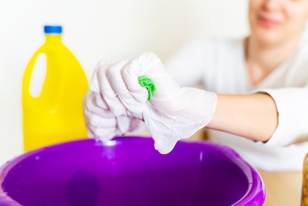 Detail van schoonmaakster die een doek met bleek afvegen om het huis te desinfecteren.