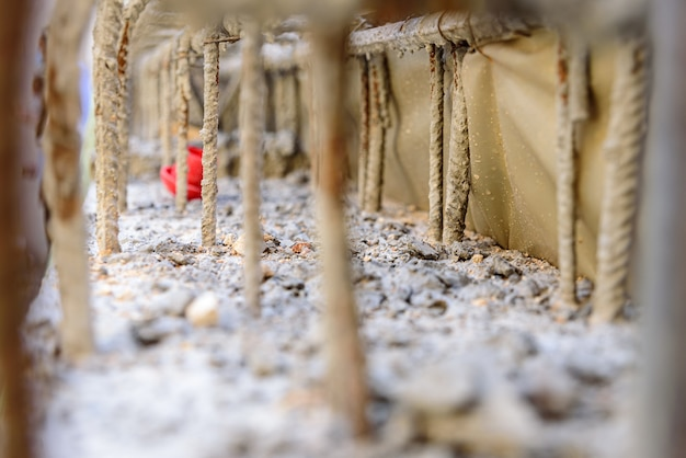 Detail van stalen staven in cement voor het gewapend beton van de funderingen van een muur van een gebouw in aanbouw