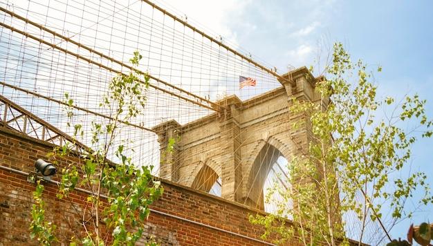 Detail van torens en amerikaanse vlag over brooklyn bridge in new york city