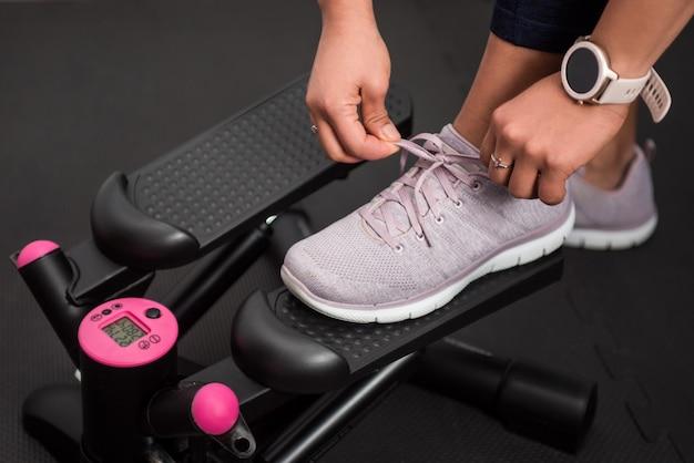 Detail van vrouw haar sneakers binden om thuis met stepper te trainen