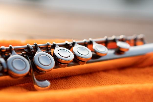 Detail van zilveren fluitsleutel die door zonsonderganglicht glanst op oranje doek
