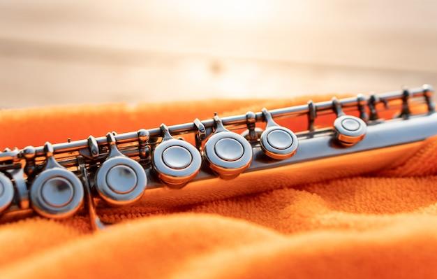 Detail van zilveren fluitsleutel die door zonsonderganglicht glanzen op oranje doek, het elegante instrument van de metaalhoutblazers voor het onderwijs van de muziekstudent