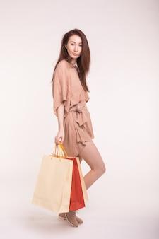 Detailhandel en verkoopconcept. lachende aziatische vrouw in jurk met veel boodschappentassen op wit