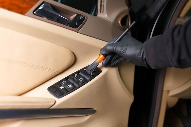 Detailing master reinigt auto-interieur met een borstel