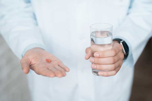 Detailopname. arts houdt rode pil en glas water.