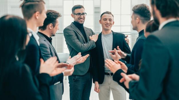 Detailopname. baas en business team feliciteren met hun collega