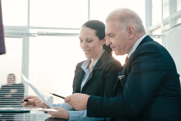 Detailopname. baas en zijn assistent bespreken zakelijke documenten. bedrijfsconcept.