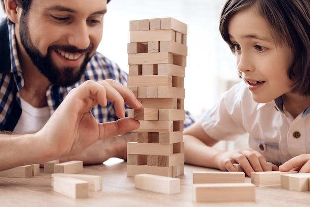 Detailopname. bebaarde vader met kleine zoon speelt jenga thuis.