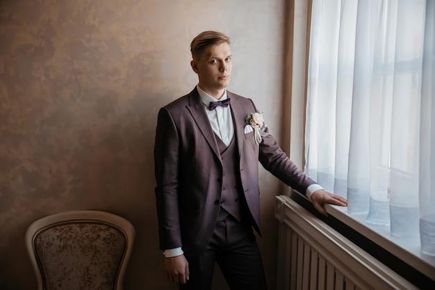 Detailopname. broeierige bruidegom die bij het raam staat