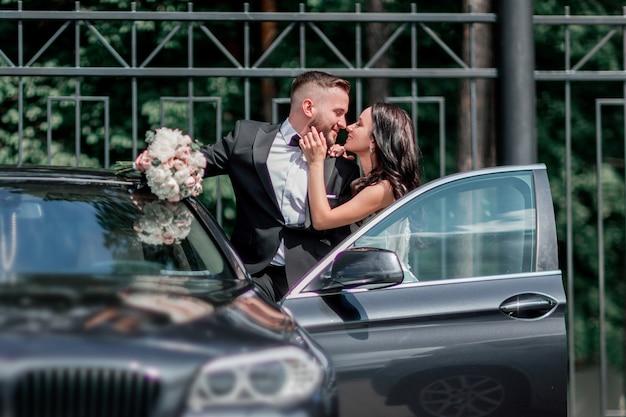 Detailopname. bruid en bruidegom staan bij de auto