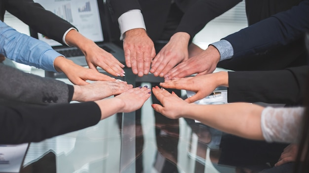 Detailopname. business team sluit zich aan bij hen in de palm van je hand boven het bureau. het concept van teamwerk