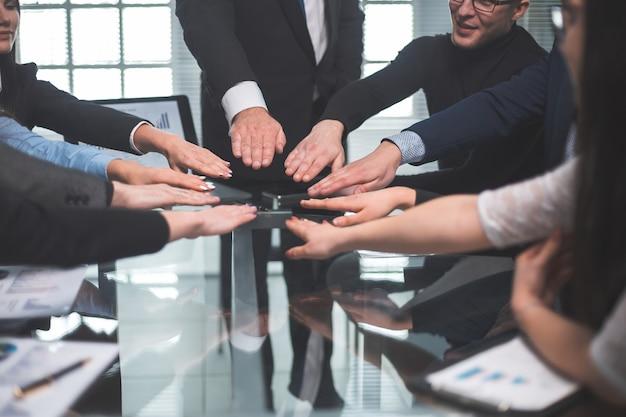 Detailopname. business team sluit zich aan bij hen in de palm van je hand boven het bureau.