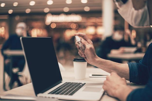 Detailopname . cafébezoeker die antisepticum op zijn laptop spuit. foto met een kopie-spatie