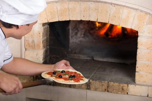 Detailopname. chef-kok steekt een pizza in de oven.