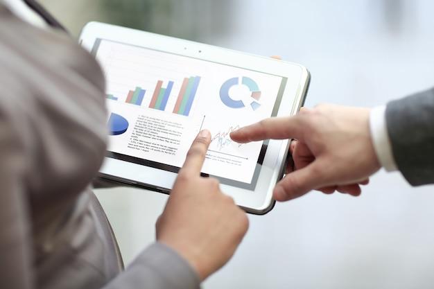 Detailopname. collega's bespreken financiële gegevens met behulp van een digitale tablet.