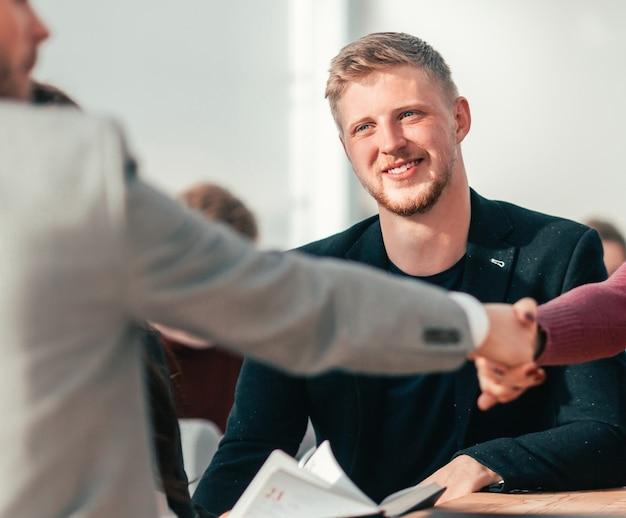 Detailopname. de gelukkige sollicitant die tijdens het sollicitatiegesprek de hand schudt van de werkgever