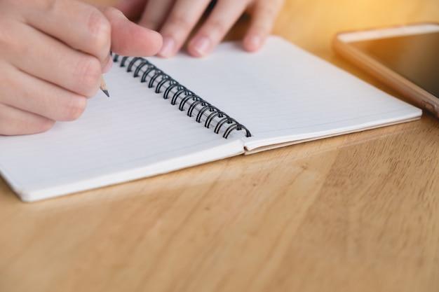 Detailopname. de hand van de vrouw schrijft op blocnote met potlood. werkend bedrijfsconcept