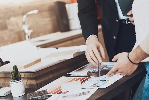 Detailopname. de mens toont materialen en blauwdrukken aan de klant.
