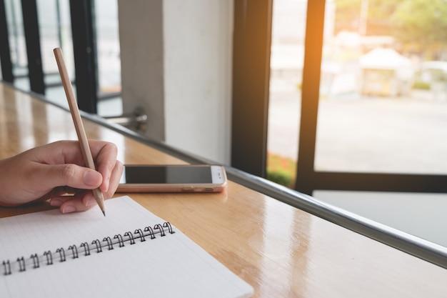 Detailopname. de vrouwenhand schrijft op blocnote met potlood naast windown, werkend bedrijfsconcept