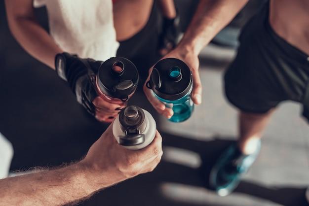 Detailopname. drie handen met flessen in de sportschool.