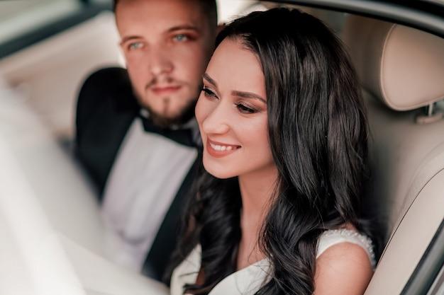 Detailopname. een gelukkig stel pasgetrouwden die in de auto zitten.