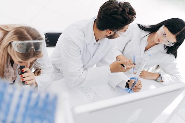 Detailopname. een groep wetenschappers doet onderzoek en maakt aantekeningen in het tijdschrift. wetenschap en gezondheid