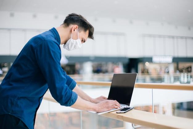 Detailopname. een jonge man met een beschermend masker die een laptop gebruikt