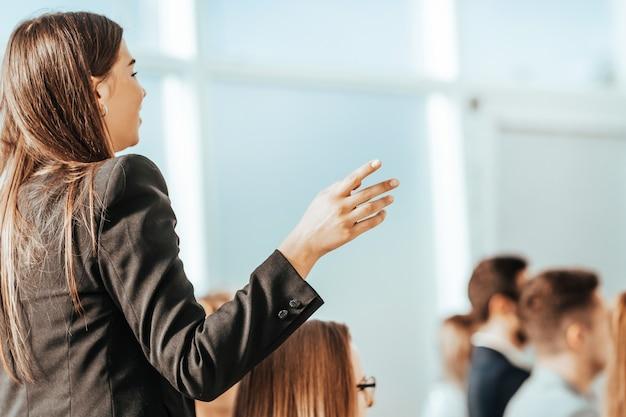Detailopname. een jonge vrouw stelt vragen aan de spreker. foto met kopieerruimte
