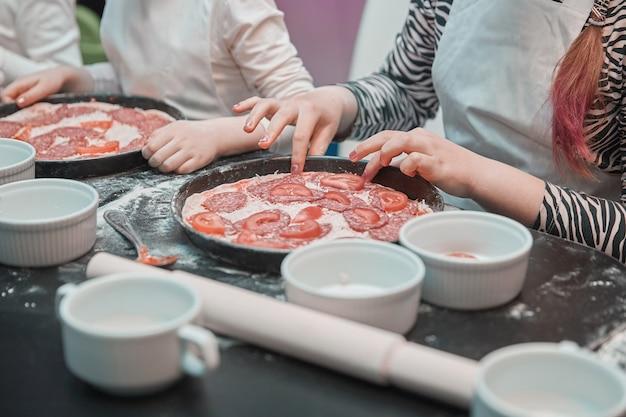 Detailopname. een klein meisje legt stukjes tomaten op basis van pizza. samen pizza bakken