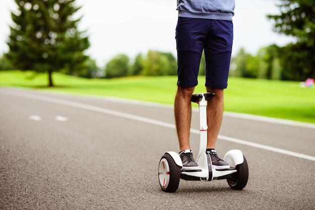 Detailopname. een man rijdt op een gyroboard door het park.