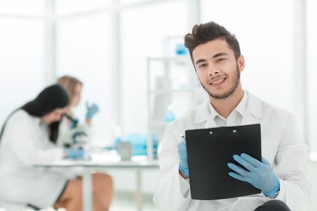 Detailopname. een wetenschapper schrijft de resultaten van een experiment in een laboratoriumjournaal. foto met kopieerruimte