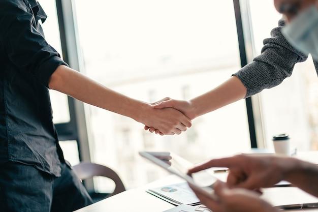 Detailopname. financiële partners van mensen met beschermende maskers die elkaar de hand schudden.