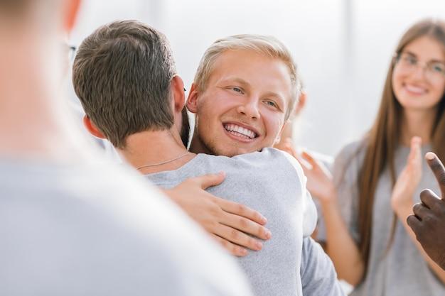 Detailopname. gelukkige deelnemers die elkaar omhelzen. succes concept