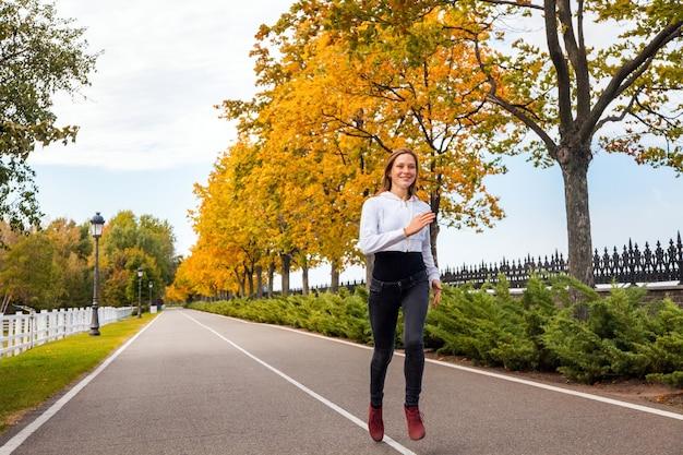 Detailopname. gezonde vrouw joggen in herfst park. buitenopname