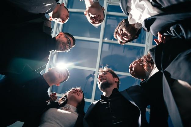 Detailopname. groep gelukkige jonge mensen uit het bedrijfsleven staan in een cirkel. bedrijfsconcept.