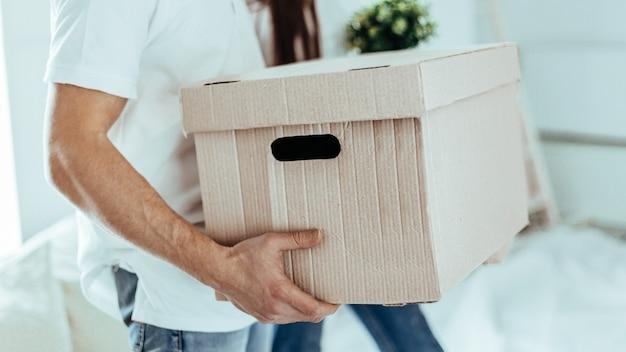 Detailopname. grote kartonnen doos in de handen van een jonge man.