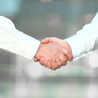 Detailopname. handdruk zakenmensen op onscherpe achtergrond. het concept van partnerschap