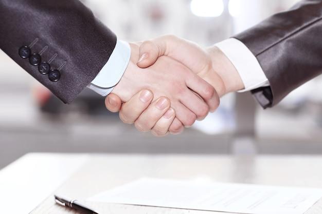 Detailopname. handdruk zakenpartners na ondertekening van het contract. concept van partnerschap