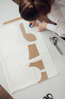 Detailopname. handen vrouw kleermaker bezig met het snijden van een rol stof waarop ze het patroon van het kledingstuk dat ze maakt met kleermakerskrijt heeft uitgetekend.