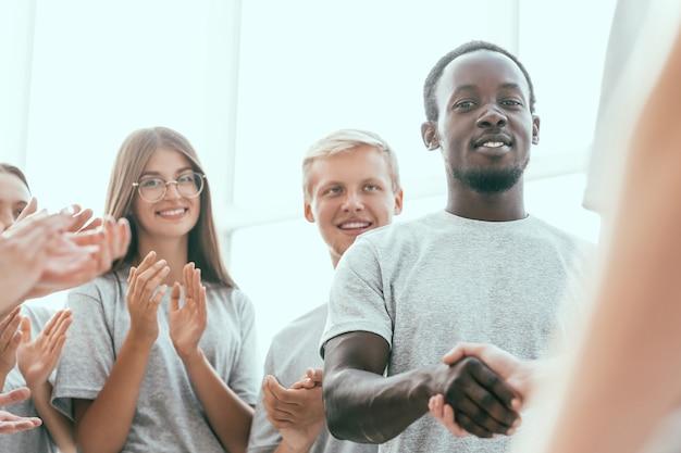 Detailopname. jonge deelnemers aan het bedrijfsseminarie handen schudden