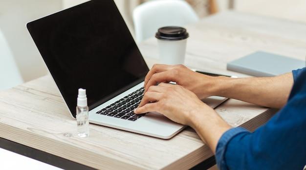 Detailopname. jonge man aan het werk op een laptop, veiligheidsmaatregelen in acht nemend. persoonlijke hygiëne en gezondheidszorg