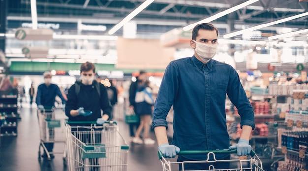 Detailopname. jonge man met een beschermend masker met een winkelwagentje
