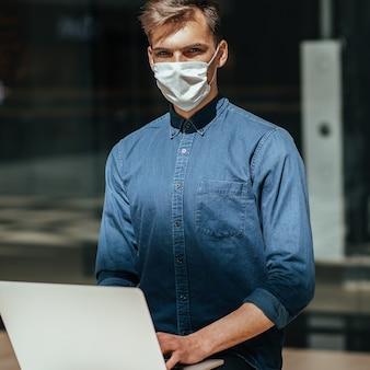 Detailopname. jonge man met een beschermend masker zittend op een bankje in de stad.