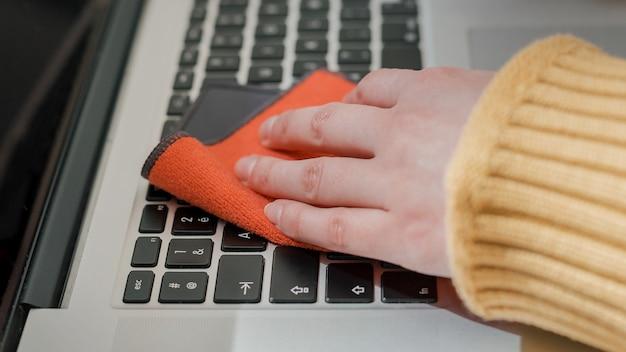 Detailopname. jonge vrouw die haar laptop behandelt met ontsmettingsmiddel