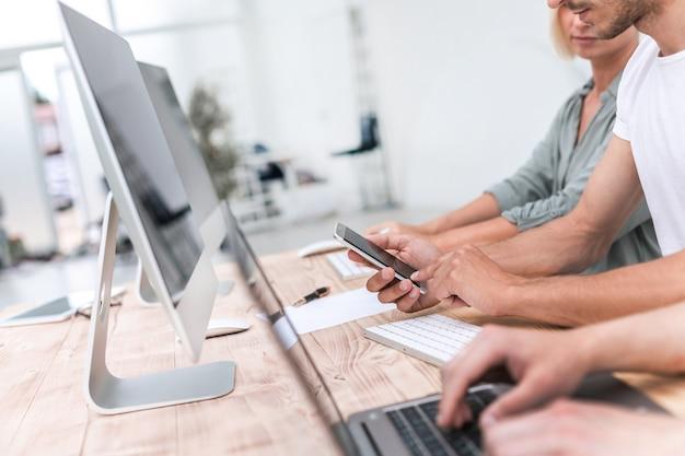 Detailopname. jonge werknemers kijken naar het scherm van zijn smartphone. mensen en technologie