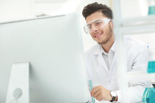 Detailopname. jonge wetenschapper kijken naar computermonitor. wetenschap en gezondheid