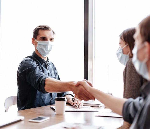 Detailopname. jonge zakenpartners in beschermende maskers die elkaar de hand schudden. concept van gezondheidsbescherming