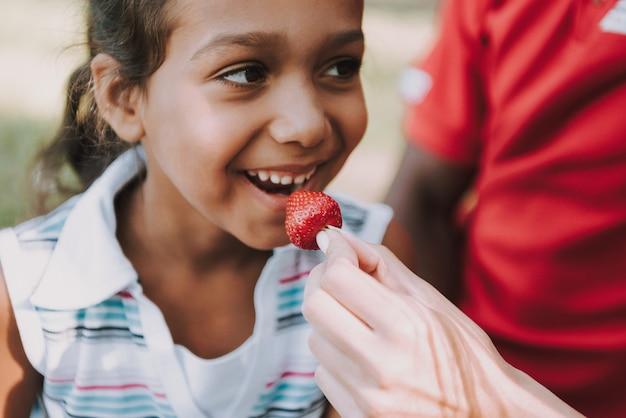 Detailopname. klein meisje eet aardbei op picknick.