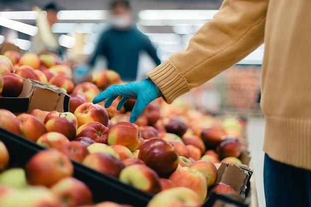 Detailopname. koper plukt appels in de winkel. veiligheidsconcept