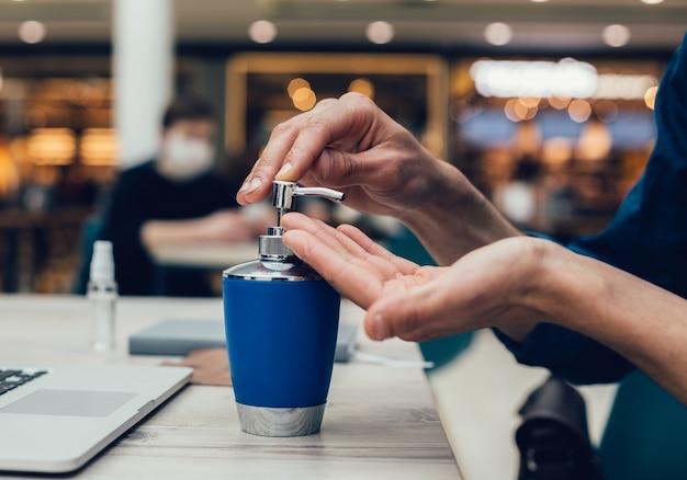 Detailopname. man die een ontsmettende gel op zijn handen aanbrengt. foto met een kopie-spatie